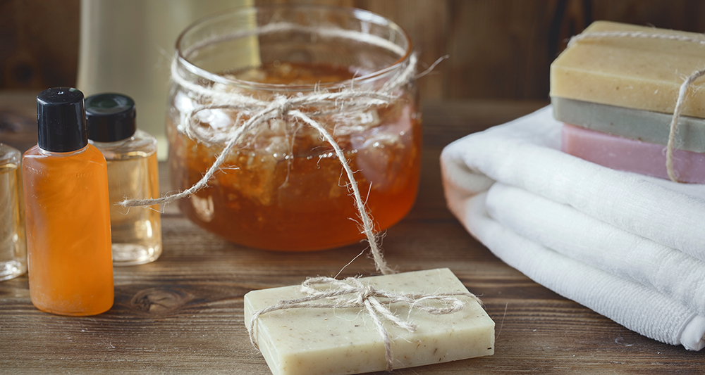 Bath towels, soaps and shampoos on a table with a jar of honey.