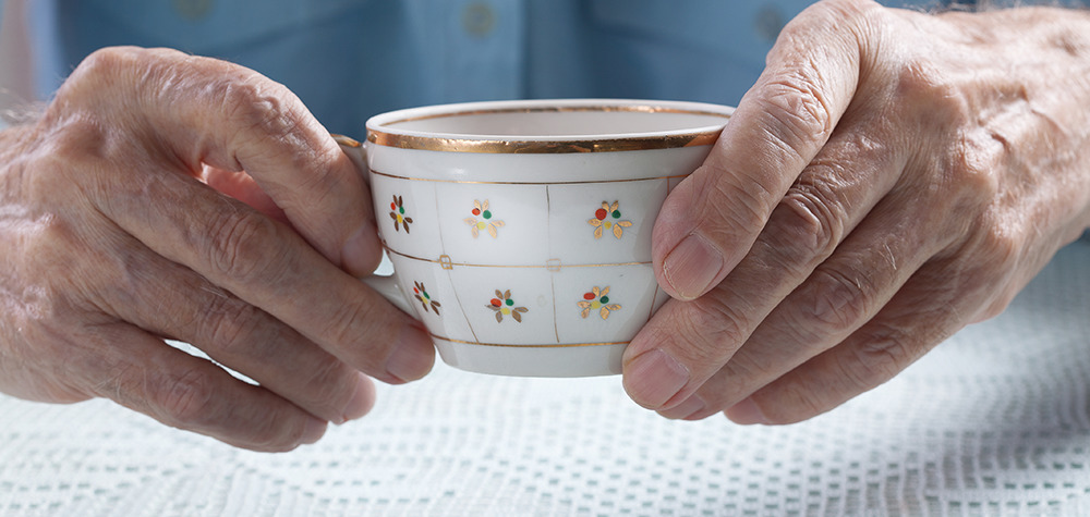 elderly hands holding tea cup