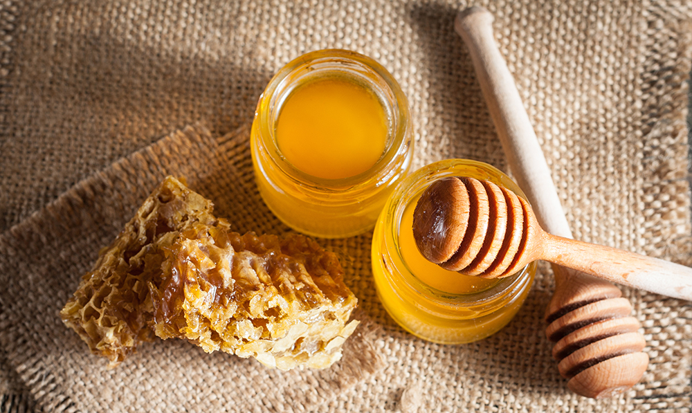 Honey in jars with honeycomb on burlap placemat
