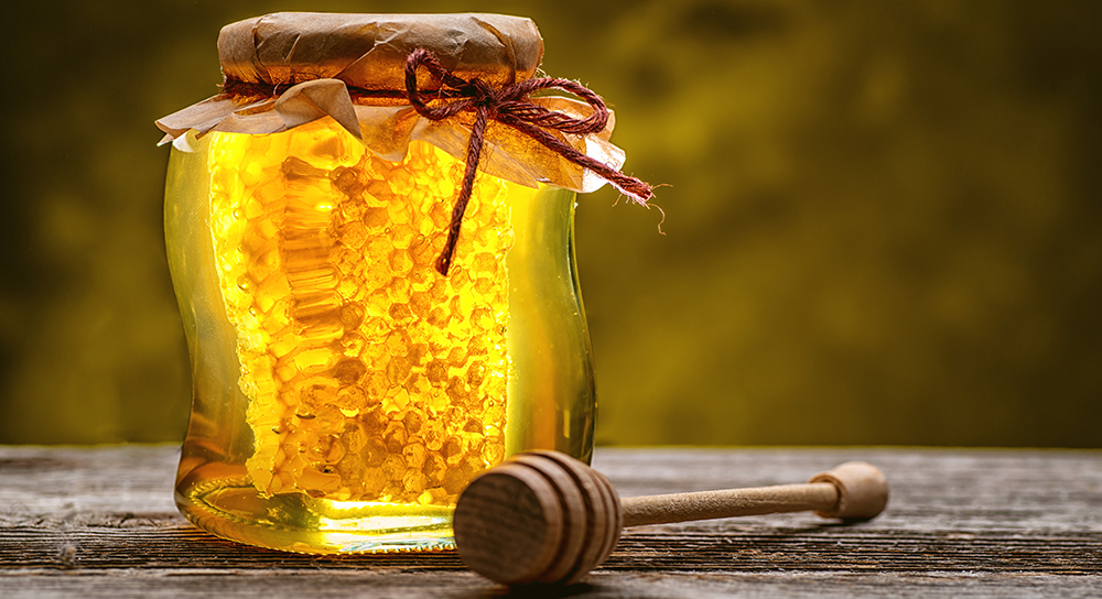 Jar of honey on table top with honey dipper
