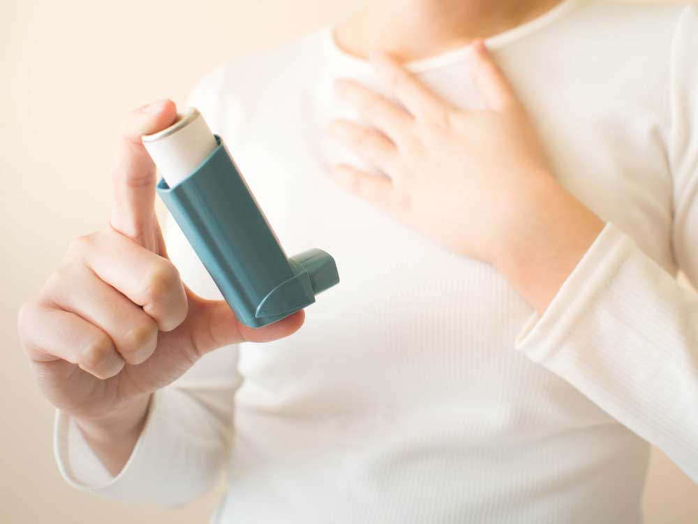 person holding asthma inhaler with hand to chest