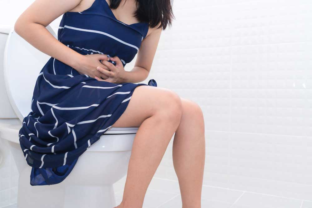 Woman sitting on toilet holding stomach