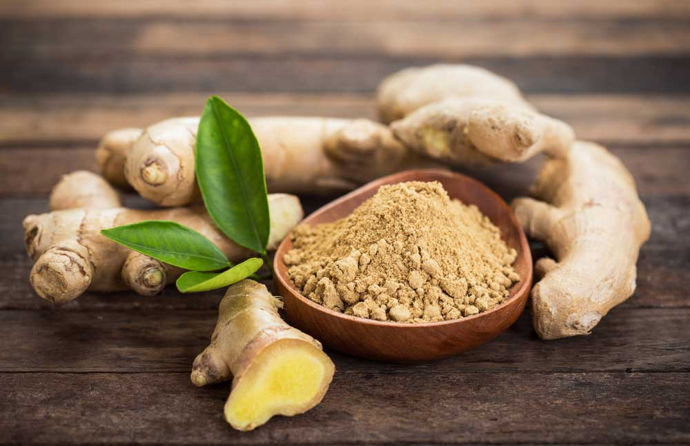 Ginger root on wooden surface with bowl of powdered ginger