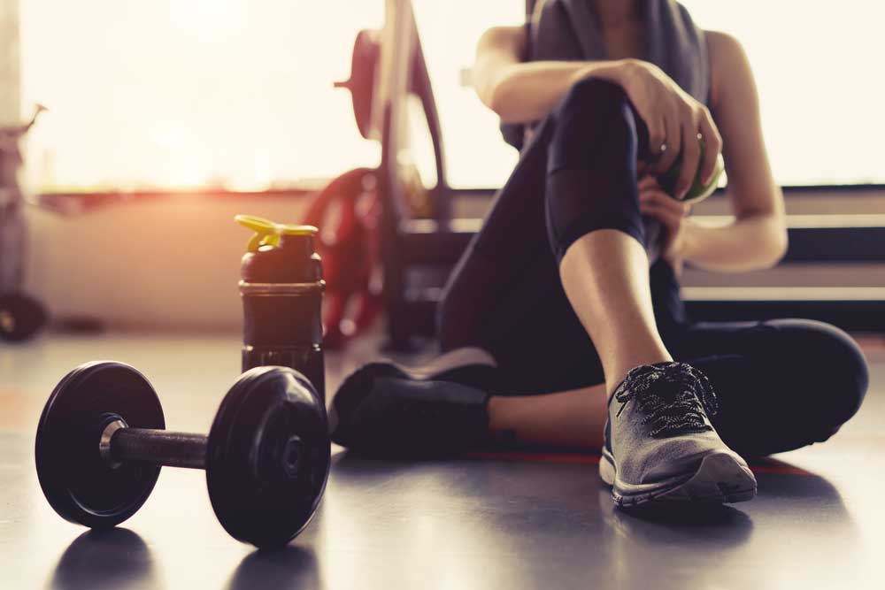 Person sitting on gym floor with water bottle and dumbell